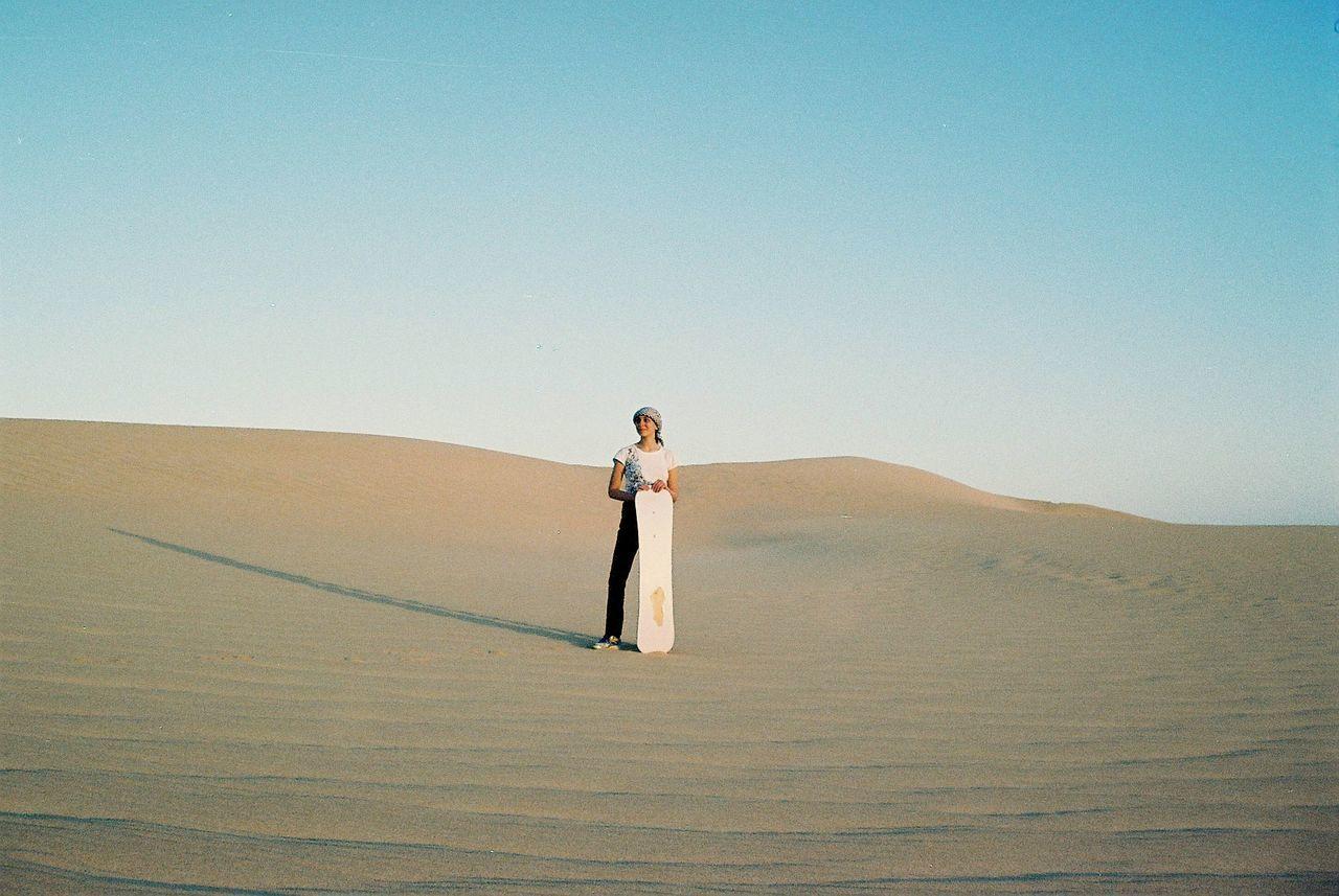 Full length of woman standing on desert against sky