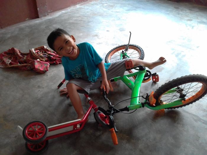A boy falling off the bike. Indoors  Home Falling Off Bike Boy Mini Scooter Moments Suddenly Smiling Portrait Happiness Full Length Cheerful Sport Exercising Looking At Camera Fun Stunt Racing Bicycle The Portraitist - 2018 EyeEm Awards The Photojournalist - 2018 EyeEm Awards
