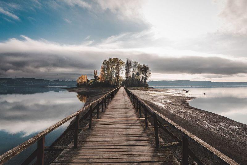 Footbridge by lake against sky