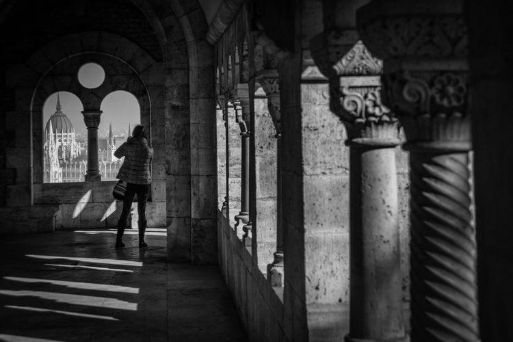 Rear view full length of woman in corridor looking at hungarian parliament building