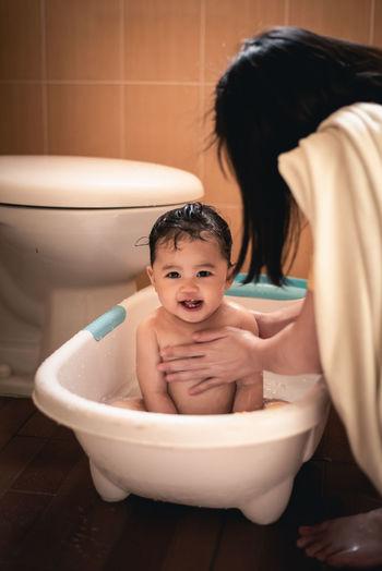Mother bathing daughter in bathtub at bathroom