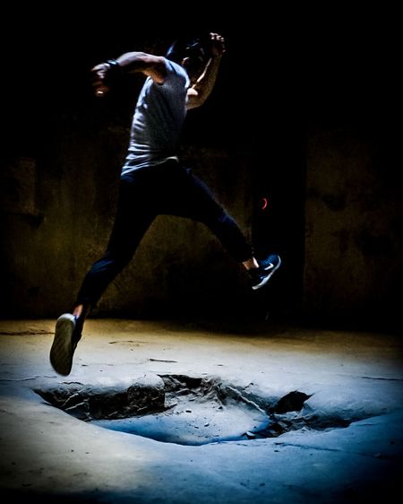 Full length of man jumping in mid-air at night