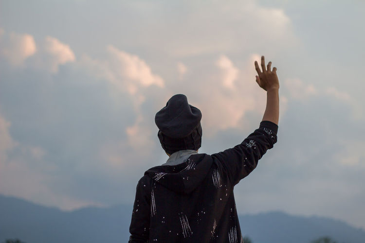 Rear view of man with hand raised standing against cloudy sky