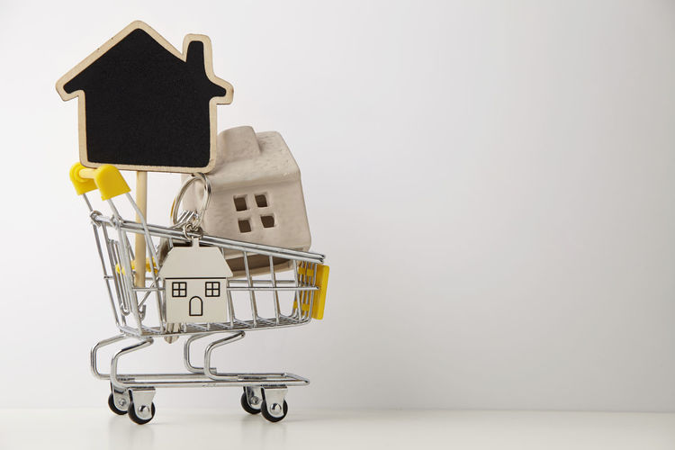Model House And Blackboard In Shopping Cart Against White Background