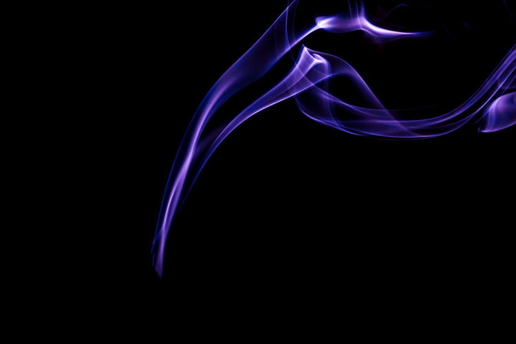 Close-up of purple smoke against black background