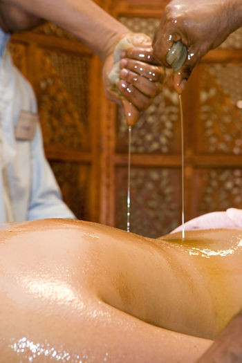 Cropped hands pouring oil on woman back in beauty spa