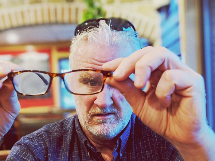 Portrait of man looking through eyeglasses at home