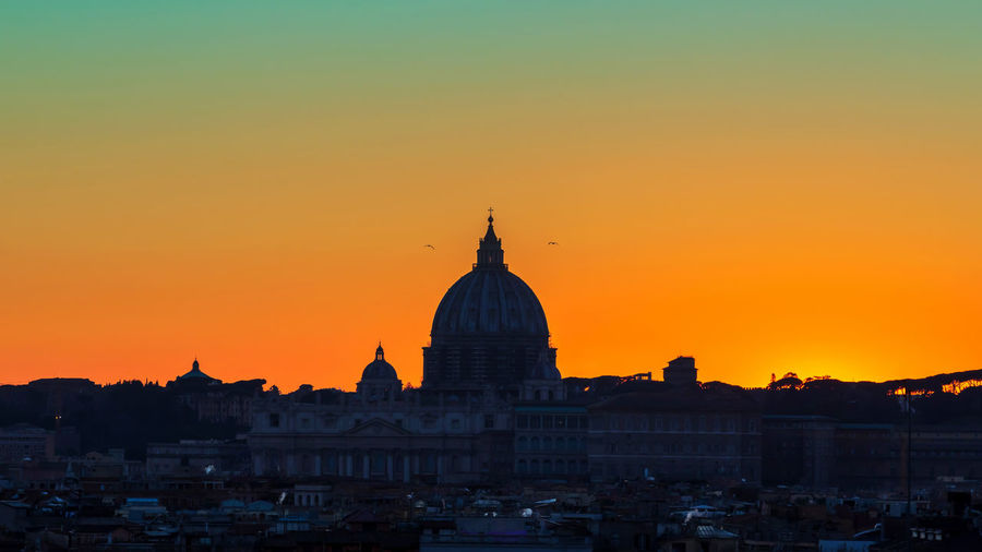 Sunset on the skyline of rome city, with the dome of st. peter's cathedral in the center.