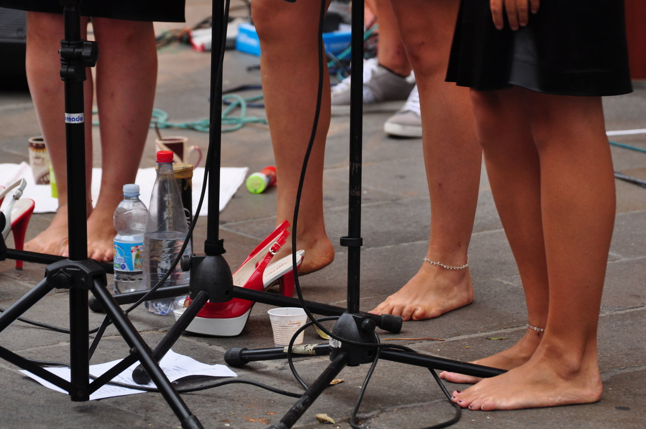 Low Section Of Singers Standing Near Microphone Stand On Street