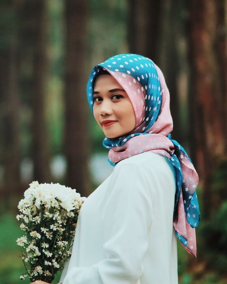 Portrait of beautiful woman wearing hijab holding flowers