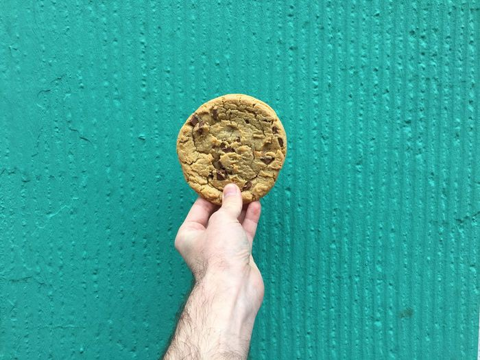 Cropped image of hand holding cookie against wall