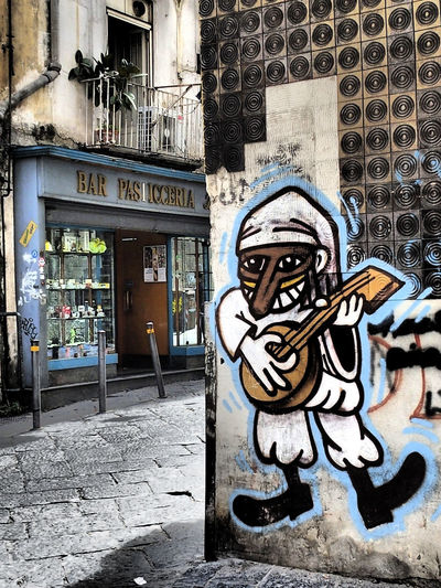 graffiti from Pulcinella in the old town of Naples with a bar in the background Graffiti Italian Street Napel Napoli Old Town Streets Art And Craft Building Exterior Graffiti Wall No People Pasticceria Pulcinella Streetart