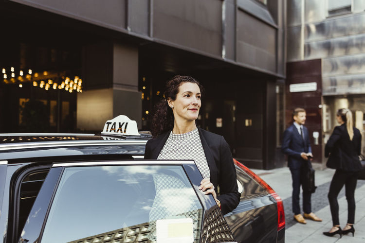 Woman standing by car in city