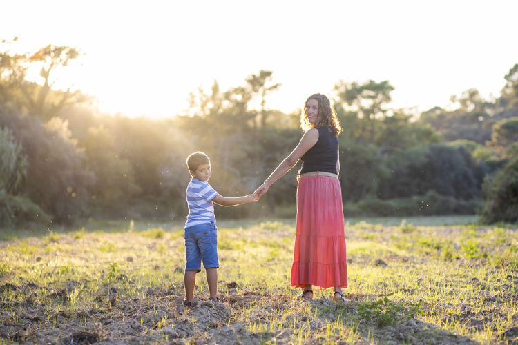 Woman and kid holding hands on a meadow