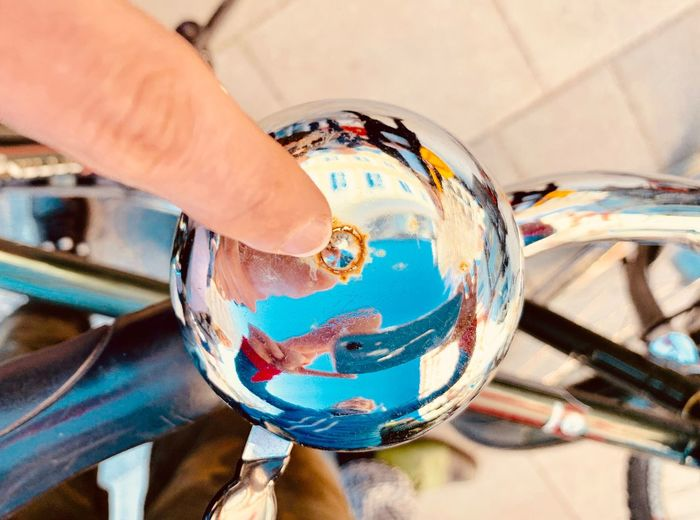 High angle view of finger on bicycle bell