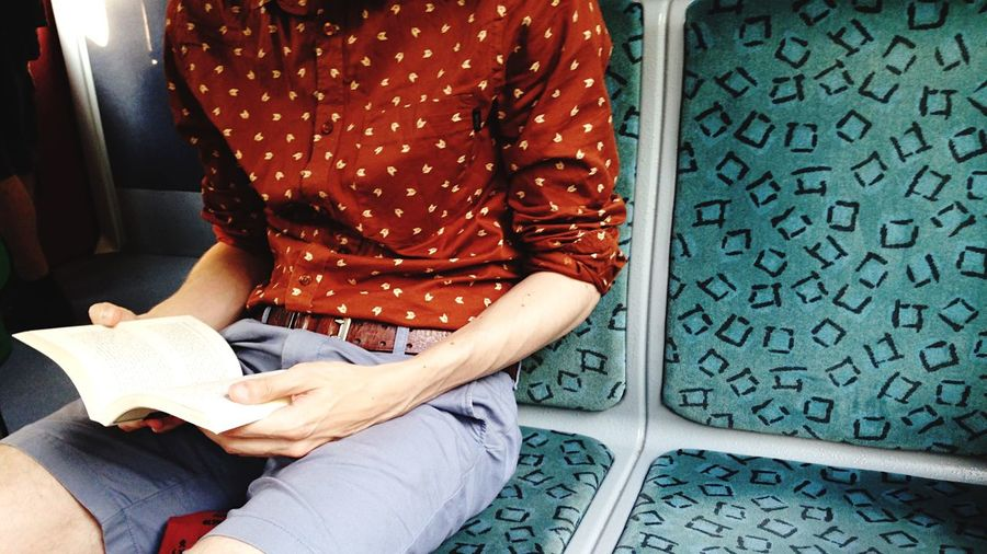 Midsection of man reading book while sitting in train