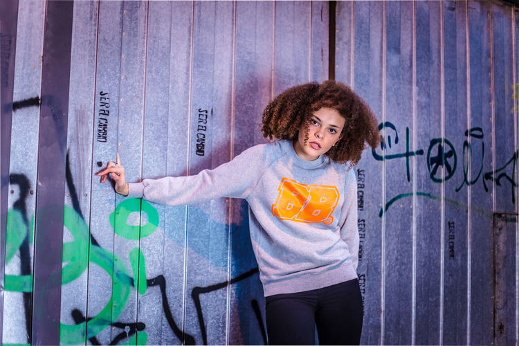 Portrait of smiling woman standing against graffiti wall