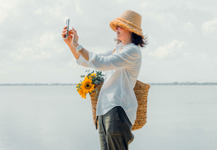 Portrait beautiful  woman in casual wearing straw hat. cheerful girl taking selfie during vacation.