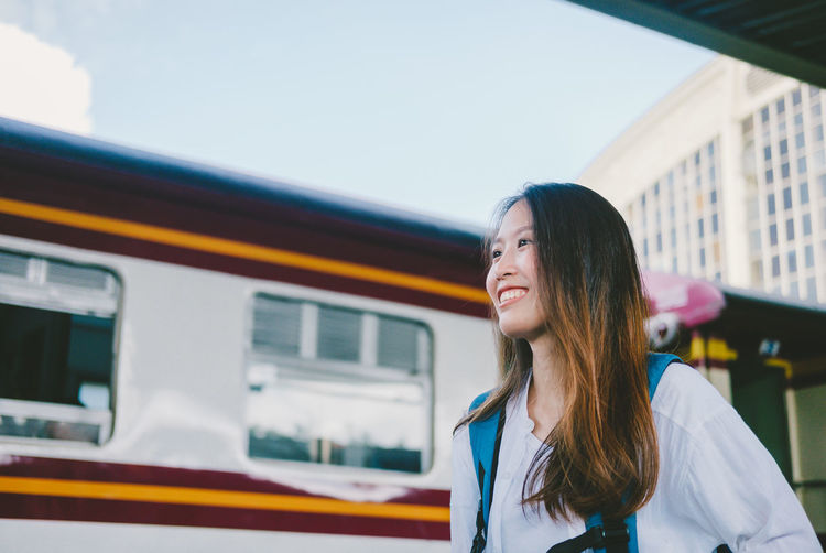 Portrait of smiling woman standing by train