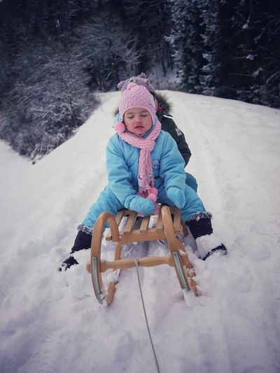 Cute siblings wearing warm clothing while sitting on sled in snow