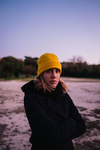 Portrait of young woman in hat standing against sky during winter