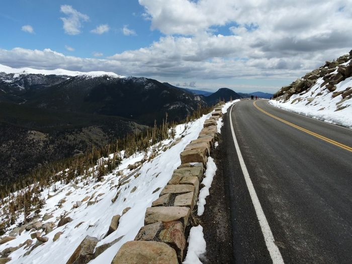 Looking down Trail Ridge Road near Rainbow Curve in Rocky Mountain National Park Colorado. Travel Alpine Alpine Road Curve Dropoff Steep Edge Mountains Mountain Road Mountain Landscape Scenic Drive Snow May 2015.