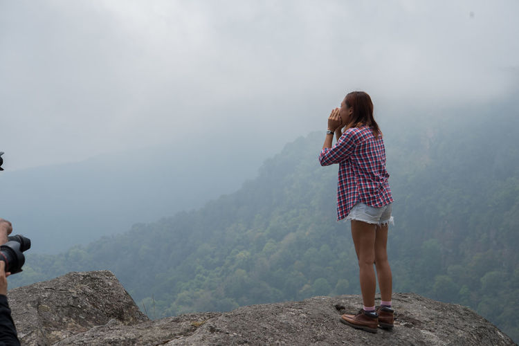 Side view of young woman screaming while standing on cliff