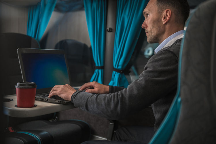 Side view of man using laptop in bus