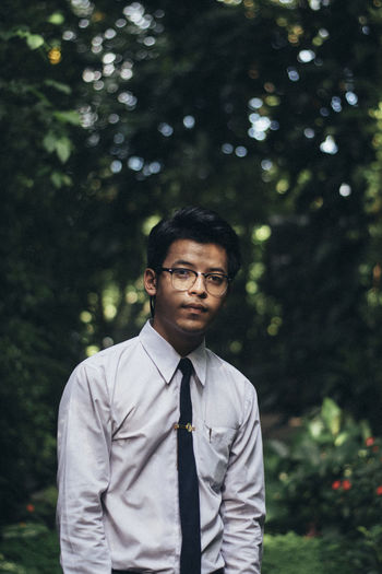 Portrait of young man standing against trees in park