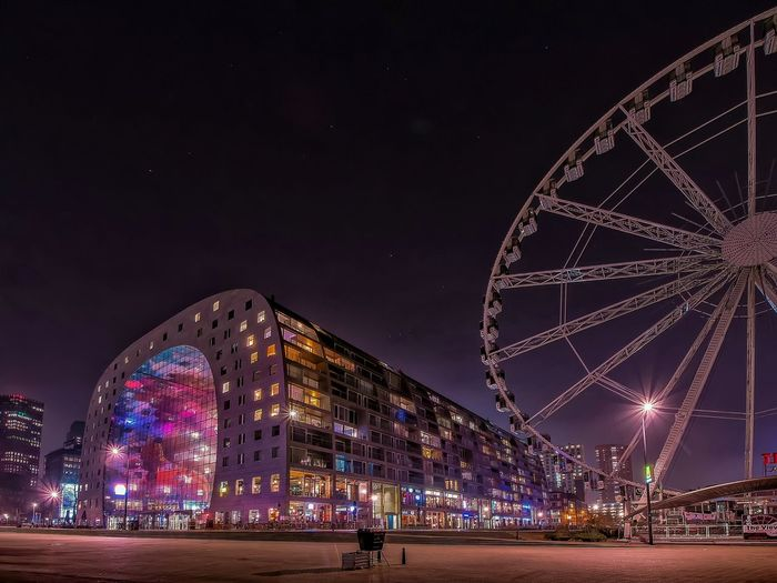Low Angle View Of Ferris Wheel And Illuminated Market Hall Sky At Night