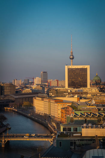 Mid distance view of fernsehturm against clear sky in city
