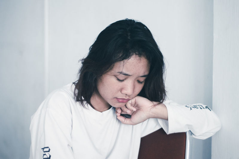 Sad young woman sitting against white wall