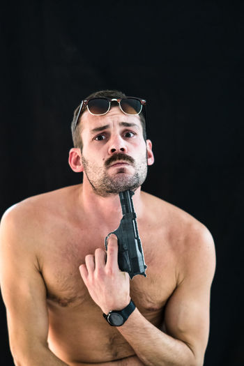 Shirtless man attempting suicide with gun against black background