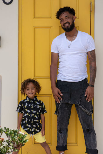 Like father like son Men Males  Casual Clothing Front View Two People Family Togetherness Emotion Child Three Quarter Length Childhood Standing Real People Lifestyles Bonding Yellow Looking At Camera Positive Emotion Son Fashion Father Fatherhood Moments