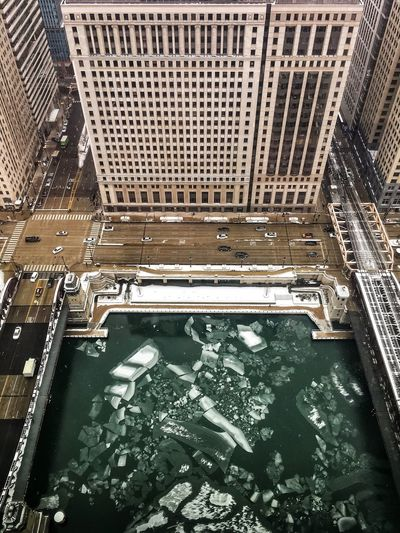 Ice floating in the Chicago River, seen from above, surrounded by Wacker Drive, riverwalk, el tracks, and light traffic. El Tracks The Loop Chicago City Streets  Buildings Up High Looking Down Perspective Snow December Cityscape Frigid Temps Winter Downtown Chicago Loop Chicago River Riverwalk Elevated Track Chicago Wacker Drive Frozen River Ice Chunks Ice Water Architecture Built Structure Sewage Day No People Building Exterior Outdoors