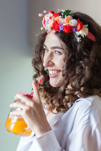 hippie young woman drinking juice with a straw Beverage Detox Studio Beautiful Woman Beauty Brunette Flower Glass Hairstyle Hippie Holding Indoors  Jar Leisure Activity Lifestyles One Person Orange Juice  Portrait Real People Smoothie Straw Vertical White Background Women Young Adult