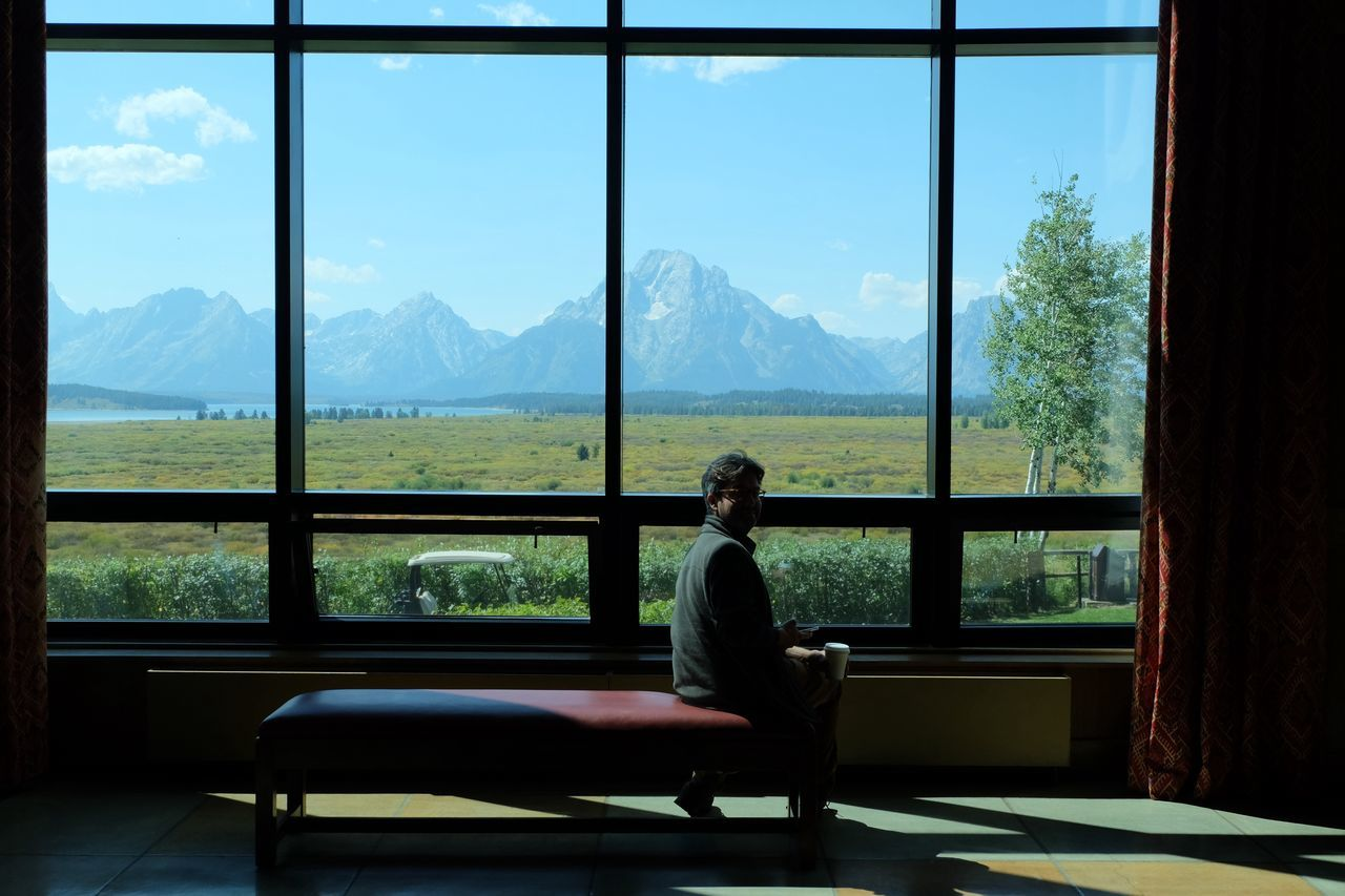 window, indoors, one person, real people, mountain, day, full length, nature, tree, lifestyles, side view, leisure activity, women, beauty in nature, relaxation, sitting, scenics, young adult, sky, people
