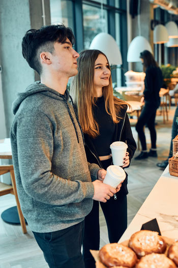 Young couple holding drink at restaurant