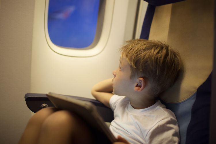 Boy Looking Away While Sitting With Digital Tablet In Airplane