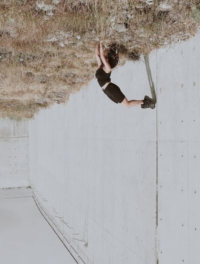 Woman jumping on wall