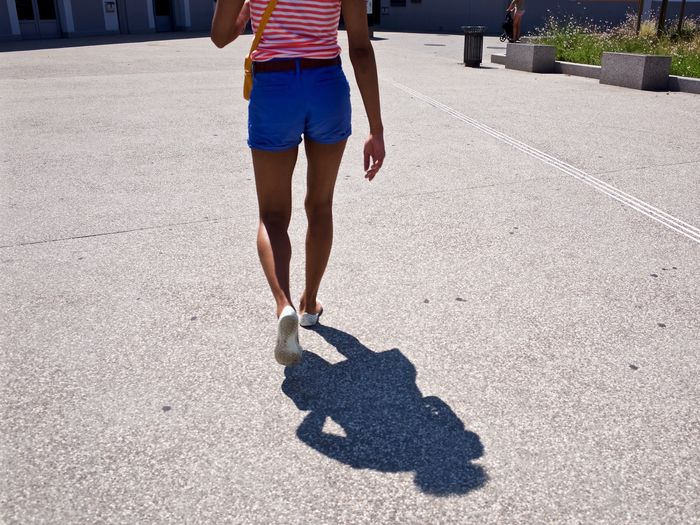 Low section of young woman walking on footpath with shadow