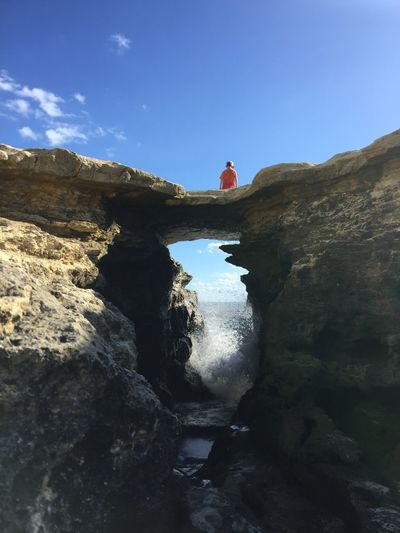 Rear view of boy standing on rock formation by sea against sky