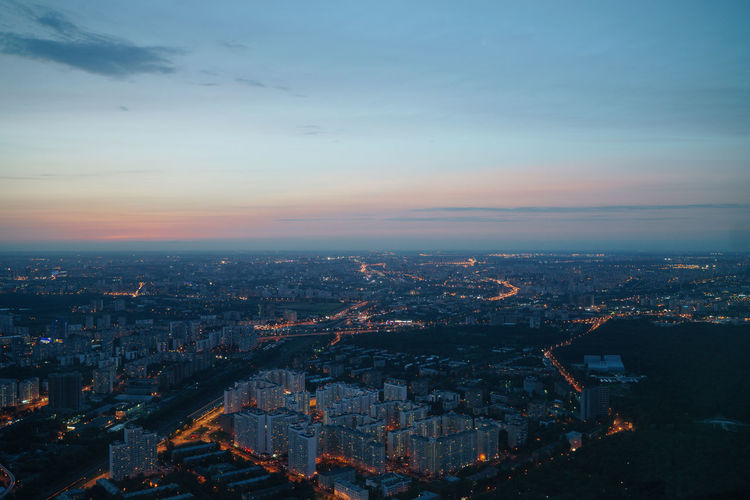 Aerial view illuminated city against sky at sunset