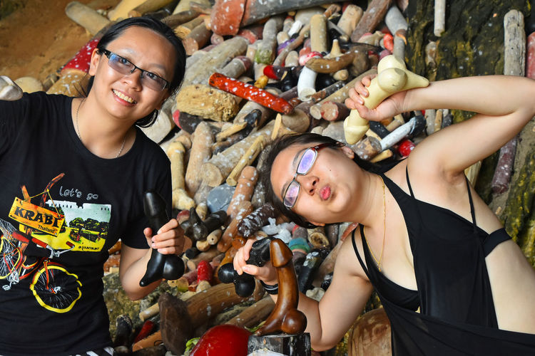 Irreverent tourists pose with wooden sacred religious attributes in front of cameras at Princess Cave shrine temple, Railay, Krabi, Thailnd, September 2015 Asian  Church Dishonor DISRESPECT Disrespectful  Irreverent Krabi Krabi Thailand Lack Of Culture Phranang Phranang Cave Pose Poser Posing Posing For The Camera Princess Cave Profanity Srine Temple Thailand Tourists Up Close Street Photography Telling Stories Differently
