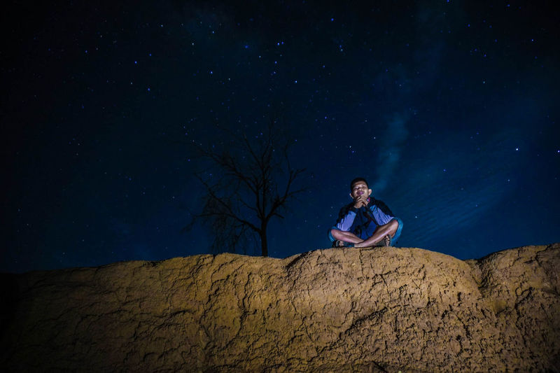 Low angle view of man sitting on rock formation against star field