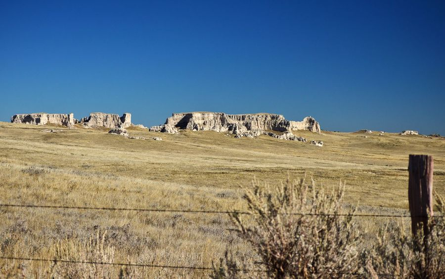 Along the ridge Shadows Pasture Rock Formations West Of Lusk Wyoming Outdoors Sunshine Barbed Wire Wooden Post Fence Clear Sky Landscape Grass