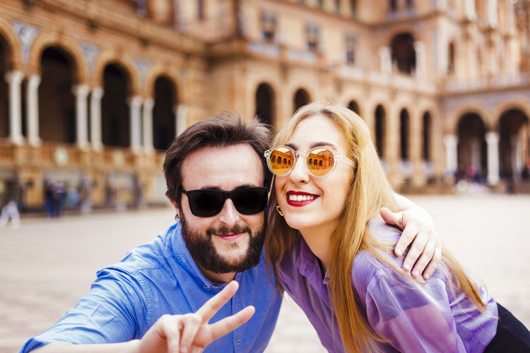 Two happy friends wearing sunglasses smile at the camera. real people
