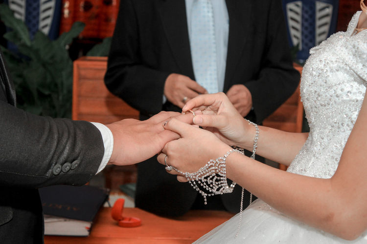 The ring finger of a man who is put on a ring by a woman in front of the priest in a holy marriage