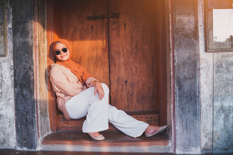 Young woman sitting on wooden door