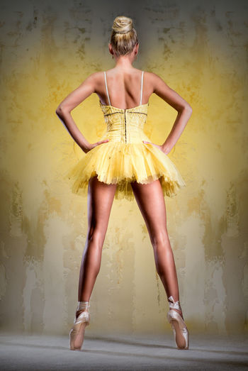 Full length rear view of ballet dancer tiptoe against yellow wall
